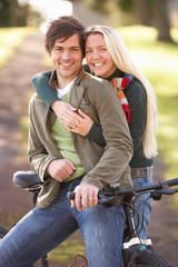 Portrait Of Young Couple With Cycle In Autumn Park