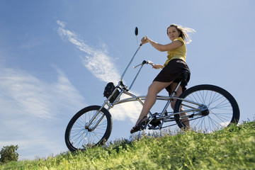 Beautiful girl cycling in the meadow