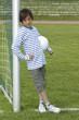 Junge mit Fussball, freundlich, am Tor angelehnt