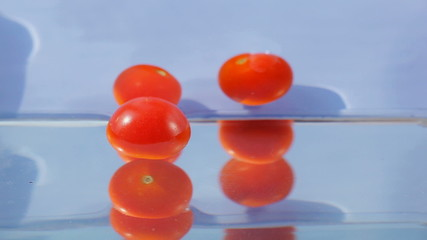 Rolling cherry tomatoes falling in water on blue background