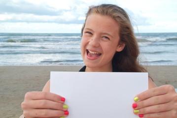 Schulferien. Eine Jugendliche am Strand mit einem Blatt Papier.