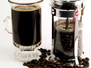 Coffee Beans, a Cup of Brewed Coffee and a Coffee Press