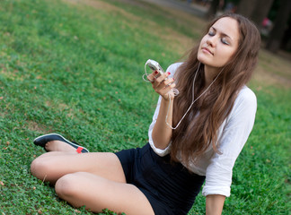 young woman listens to music in ear-phones