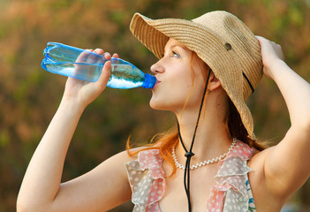 Beautiful girl in straw hat drinks water from bottle