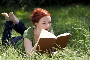 femme littéraire lisant livre dans l'herbe