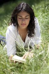 jeune fille seule lisant livre dans herbe