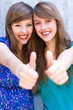 Young women giving thumbs up