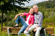 Älteres Paar auf einer Bank in der Natur