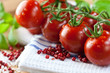Fresh cherry tomatoes and pink peppercorns on kitchen towel