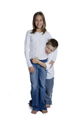 Young boy and girl hugging, studio shot isolated on white
