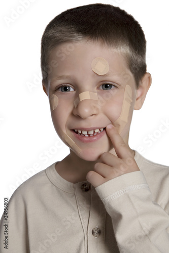 Young boy with band aids on face, studio shot isolated on white