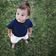 Small baby standing on the grass looking up