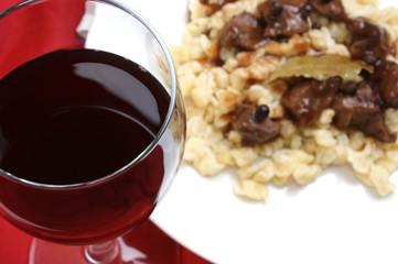 Rotwein im Glas mit Wildgulasch  im Hintergrund