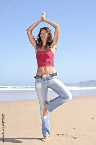 Young fit woman doing exercises at the beach