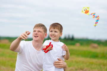 Father and son fly a kite together in summer field
