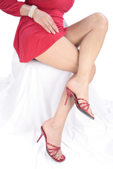 Woman legs and red dress over white background