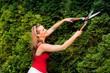 Frau schneidet die Hecke im Garten