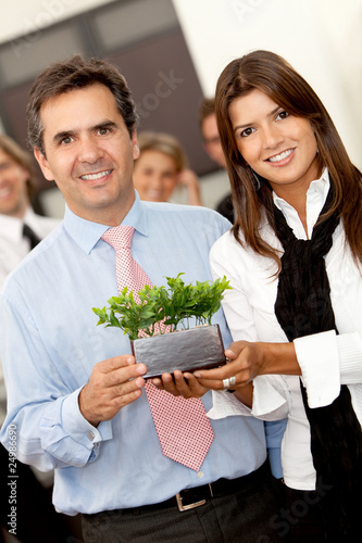 Business couple holding a plant