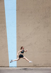 Very fit woman runs and jumps high