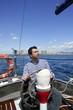 blue sailor on vintage wooden sailboat ocean sea