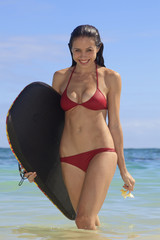 young woman at the beach in hawaii with her boogie board