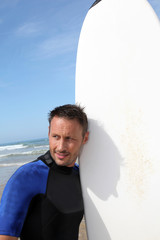 Man standing in water with surfboard