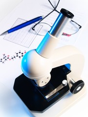 microscope, pen and glasses on white background