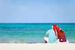Romantic couple in Santa hats sitting on tropical beach