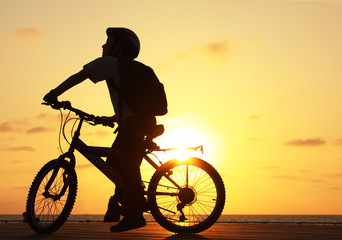 Silhouette of teenager riding bicycle