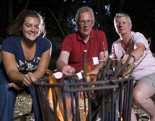 Family at campfire in the garden with marshmallows