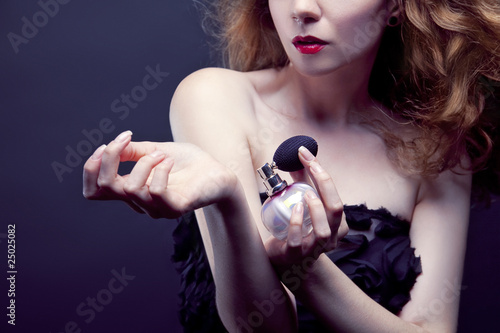 beautiful woman applying perfume on her body - 25025082