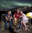 Family at campfire in mountains with northern lights