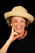 Up-close face of wrinkled elderly lady with hat on and big smile