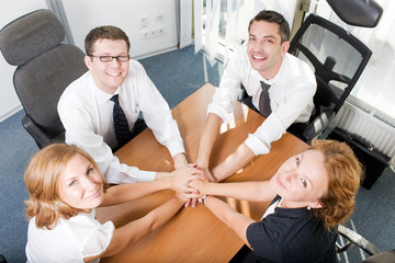 Office workers hold hands together