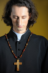 conceptual portrait of Praying priest with wooden cross praying.