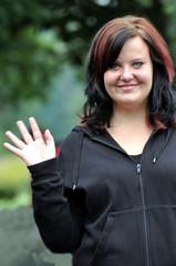 Eine junge Frau winkt