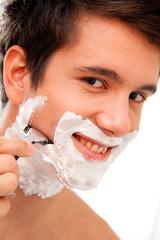 Mann rasiert sich mit Rasierklinge Und Rasierschaum