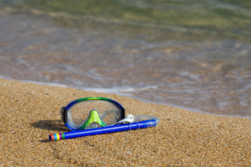 Tube and mask for a scuba diving on seacoast with a pebble