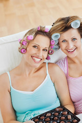 Delighted women wearing hair rollers eating chocolate looking at