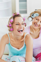Laughing women wearing hair rollers sitting on the sofa