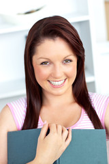 Cheerful young woman holding a book looking at the camera