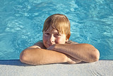 child rest on his elbow at the edge of the pool poster
