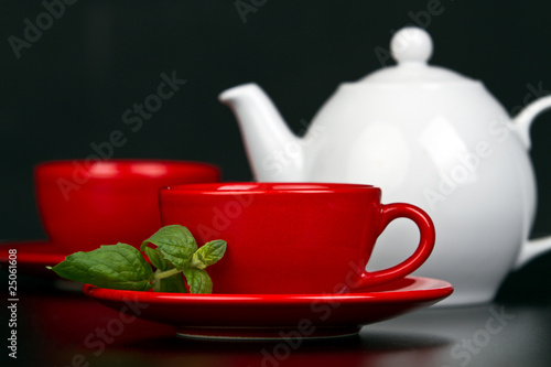 Red cup with mint and white teapot