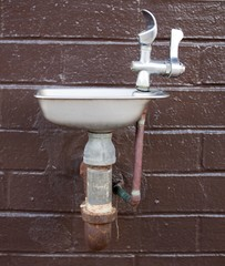school water fountain with a brick background