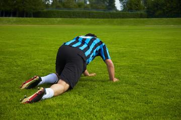 Fußballspieler kriecht auf dem Boden