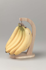 bunch of bananas hang on a wooden holder