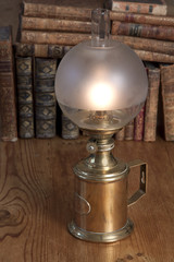 Lit vintage oil lamp with old books in the background