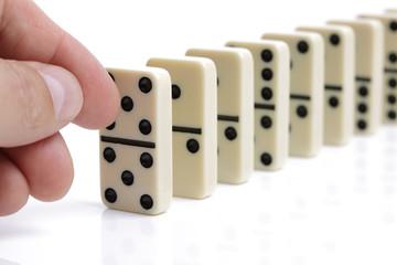 Hand pushing white dominoes