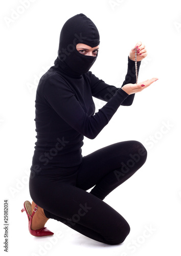 female thief in balaclava keeping bracelet