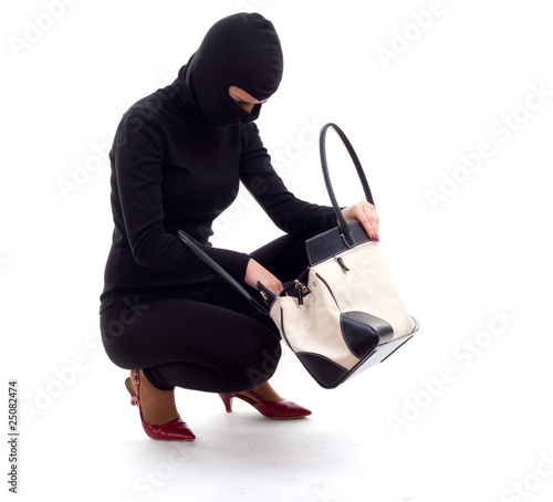female thief in black balaclava with stolen bag